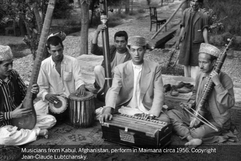 Five men sit barefoot on a rug outdoors in Afghanistan and perform on various native instruments.