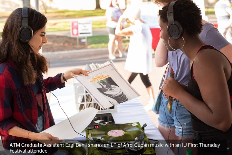 An ATM Graduate Assistant enjoys an LP of Afro-Cuban music with another student at an IU festival.